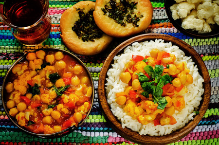 Photo pour rice with curry chickpeas with vegetables and Arabic flat bread with herbs on a multicolored background. tinting. selective focus on the middle of the rice - image libre de droit