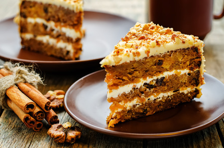 Foto de carrot cake with walnuts, prunes and dried apricots on a dark wood background. tinting. selective focus - Imagen libre de derechos