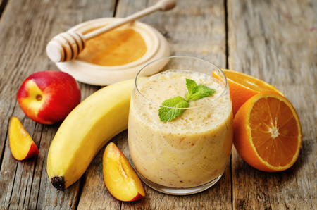 Foto per smoothies with peaches, banana and orange. the toning. selective focus - Immagine Royalty Free