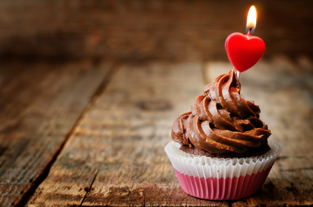 Photo pour chocolate cupcake with a candle in the shape of a heart - image libre de droit