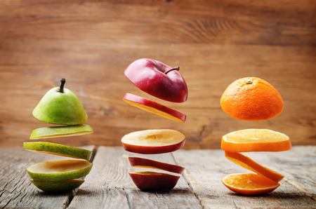 Foto de flying slices of fruit: apple, pear, orange on a dark wood background. toning. selective Focus - Imagen libre de derechos