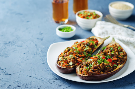 Foto de Minced meat quinoa vegetables stuffed eggplants on a stone background. toning. selective focus - Imagen libre de derechos