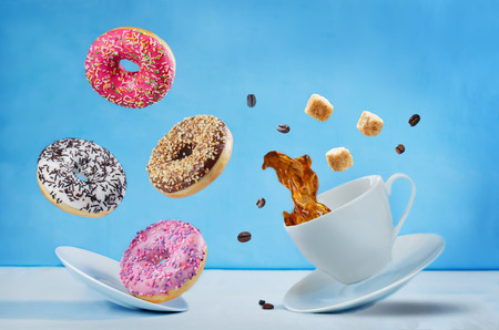 Photo for Flying cup of coffee with multicolored donuts - Royalty Free Image