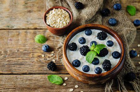 Photo pour Oatmeal porridge with fresh blueberries and blackberries. toning. selective focus - image libre de droit
