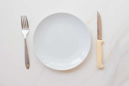 Photo pour  Empty white plate with cutlery on a marble table, saucer, fork and knife. The concept of diet, fasting. - image libre de droit
