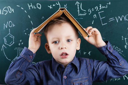 Portrait of little boy tired of studying with a book on his head in front of a green blackboard with formulas. Genius boy near blackboard with formulas. Funny portrait clever pupil boy on school board background. Back to school