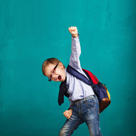 Photo pour Cheerful smiling little boy with big backpack jumping and having fun against blue wall. Looking at camera. School concept. Back to School - image libre de droit