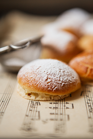 Homemade profiteroles on the music sheet with notes. Profiteroles (choux à la crÚme) - French choux pastry balls filled with custard or cottage cheese sprinkled with powdered sugar