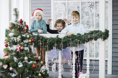 Photo pour Little children In anticipation of new year and Christmas. Three little Kids are having fun and playing near Christmas tree in interior with Christmas decorations - image libre de droit