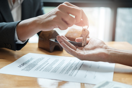 Photo pour estate agent giving house keys to man and sign agreement in office - image libre de droit