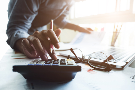 Photo pour Close up of businessman or accountant hand holding pen working on calculator to calculate business data, accountancy document and laptop computer at office, business concept - image libre de droit
