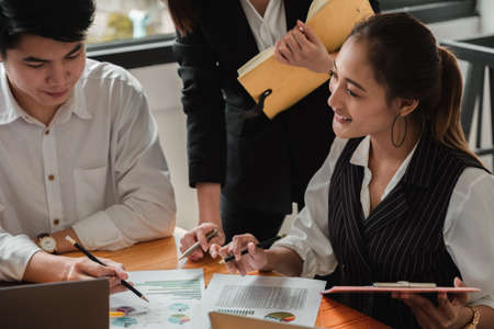 Foto de Business people are meeting together at the wooden working desk surrounded by paperwork - Imagen libre de derechos