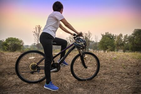 Photo for woman riding  bicycle  on the sunset in the park. - Royalty Free Image