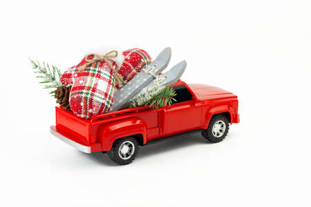 Foto de Winter holydays vacation concept. Red pickup toy with skis, gloves, suitcase, fir branch, fir cone in the trunk. Part of set. - Imagen libre de derechos