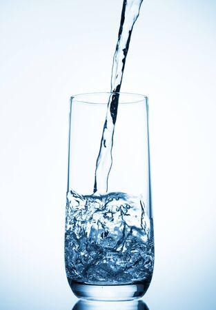 Photo pour water pouring into glass on blue background - image libre de droit
