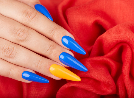 Foto de Hand with artificial manicured nails colored with blue and orange nail polish on textile background - Imagen libre de derechos