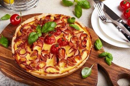 Photo for Quiche open tart pie with ham and tomatoes filled with cream, cheese and eggs. Savory taste. - Royalty Free Image