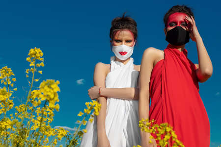 Photo pour Two beautiful young brunette girls with creative bright makeup in tunics on a background of a field of yellow flowers and blue sky. One girl in a mask, the other girl closes her mouth with her hand. - image libre de droit