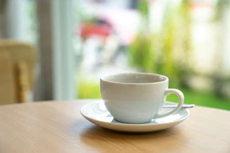 Photo pour white coffee cup on wooden table with coffee shop background. - image libre de droit