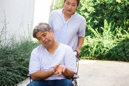Photo pour An elderly asia ; midle - aged man patient sit on a wheelchair ,his wife take care for him . Health and Medical concept. - image libre de droit