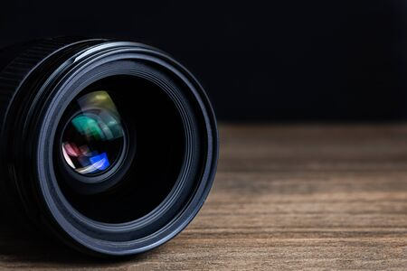 Photo for Closeup camera lens on a wooden floor with black dark background blur detail object isolated - Royalty Free Image