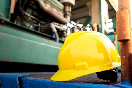 Foto für Yellow hardhat or safety helmet is placed on working platform of pumping unit in oil field operation. Selected focus on the hard hat. Safety, no accident in workplace concept photo. - Lizenzfreies Bild
