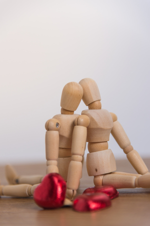 A couple of wooden doll man with heart-shaped chocolate are in love with each other