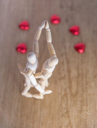 A wooden doll man on valentine day on the wooden floor with the act of love and relation. the focus is either on the doll or the heart shaped chocolate