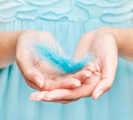Photo pour Woman's hands with feather close-up - image libre de droit