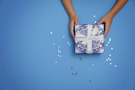 Foto de Gift in childs hands on a blue festive background - Imagen libre de derechos