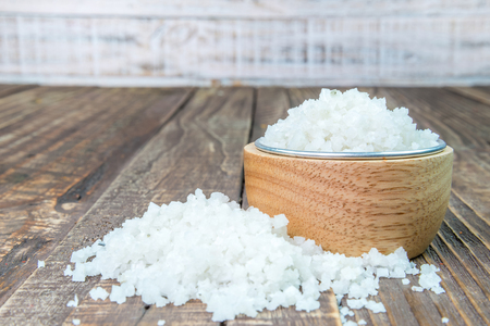 Salt in a cup on a wooden background.