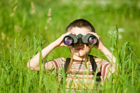 Photo pour Young boy in a field looking through binoculars - image libre de droit