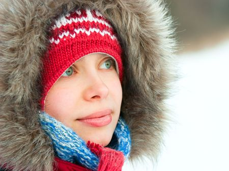 Young woman wearing furry hood and winter hat