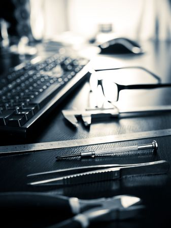 Screwdriver, pincers, ruler, caliper with keyboard and glasses on a table, very shallow DOF