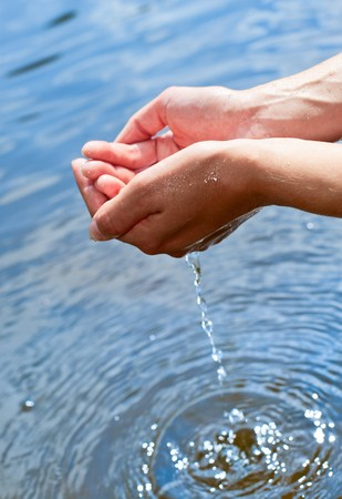 Water pouring out of a young woman's hands