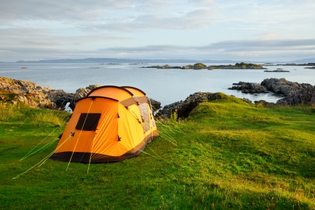 Orange camping tent on a shore in a morning light