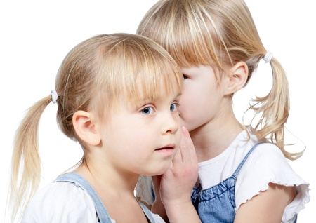 Photo pour Portrait of little girl  telling a secret to her friend over a white background - image libre de droit