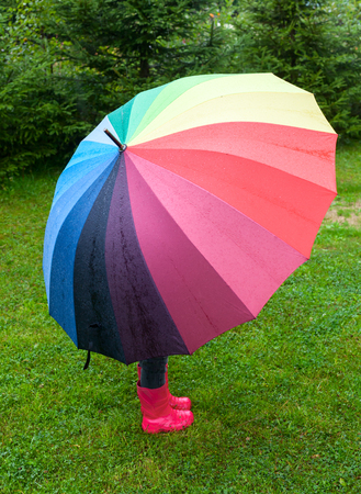 Little girl wearing red rubber boots hiding behind colorful umbrella in the rainの写真素材