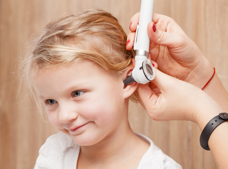 Photo pour Female pediatrician examines little girl's ear. Doctor using a otoscope or auriscope to check ear canal and eardrum membrane. Child ENT check concept - image libre de droit