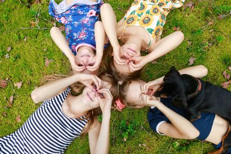 Photo for Girls of different age lying together on a moss in a summer forest enjoying summer holidays outdoor - Royalty Free Image