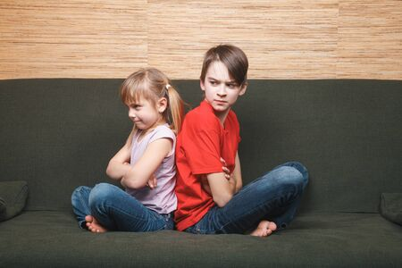 Photo for Siblings sitting on sofa unable to leave home locked in during self-isolation. Coping with quarantine and lockdown protective measures against spreading of coronavirus pandemic disease concept - Royalty Free Image
