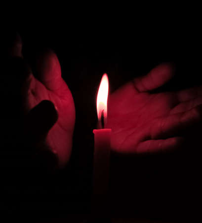 Photo for Hands supporting flame of candle at night. - Royalty Free Image