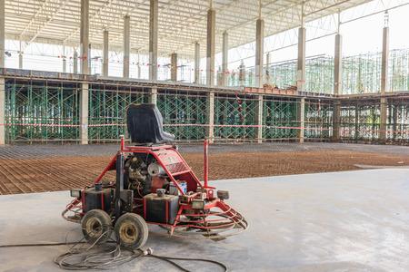 Double power trowel finishing concrete floor at construction building site , smooth concrete surface.