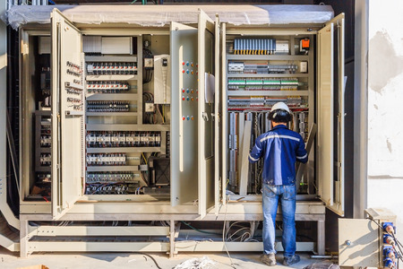 Photo for Instrument technician on the job check wiring on PLC cabinet - Royalty Free Image