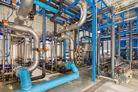 Photo pour Large industrial water treatment and boiler room. Shiny steel metal pipes and blue pumps and valves. - image libre de droit