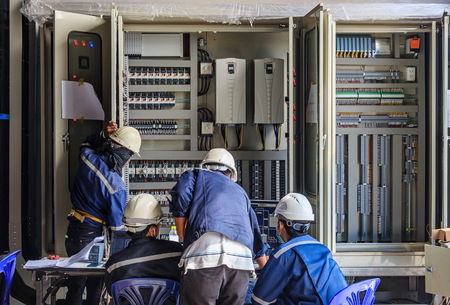 Photo pour Engineer working on checking and maintenance equipment at wiring on PLC cabinet, Engineer checking status step up transformer - image libre de droit