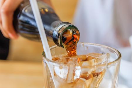 Foto für Close up of Pouring cola in a glass from a bottle - Lizenzfreies Bild