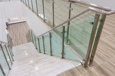 Photo for Modern white marble stairs with steel and glass railing in a new modern building. - Royalty Free Image