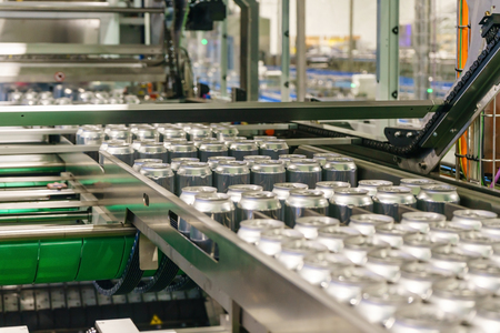 Photo pour Packed cans on the conveyor belt in berverage factory - image libre de droit