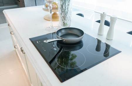Photo pour Frying pan on modern black induction stove, cooker, hob or built in cooktop with ceramic top in white kitchen interior - image libre de droit